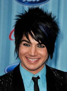 Adam Lambert picture wearing a light blue shirt under a black suit jacket matched with a black neck tie