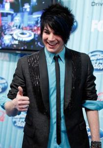 Adam Lambert wearing a blue shirt under a black suit jacket matched with a black neck tie