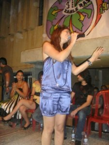 Diala Ouda wearing a blue satin top and shorts on stage singing live to her fans during a celebration in jordan 5
