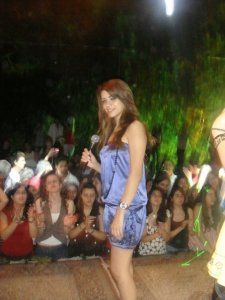Diala Ouda wearing a blue satin top and shorts on stage singing live to her fans during a celebration in jordan 6