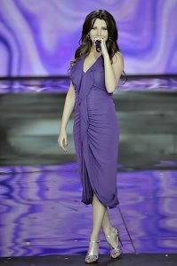 Nancy Ajram pictures performing on stage during the Miss Lebanon 2009 beauty pageant on June 29th 2009 wearing a dark purple dress 5