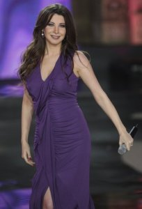 Nancy Ajram pictures performing on stage during the Miss Lebanon 2009 beauty pageant on June 29th 2009 wearing a dark purple dress 4