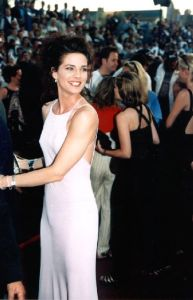 Terry Farrell wearing a sleevless white dress