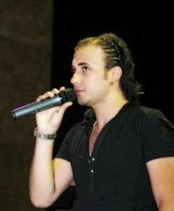 Mohamad Qwaider photo singing on stage during a concert with a long hair style