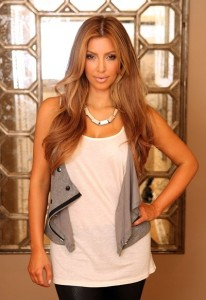 Kim kardashian picture from August 2009 photoshoot of her new high lighted hair style in a white top under a gray vest