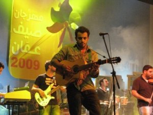 Basel Khoury picture while playing the guitar and performing on stage at a concert 12