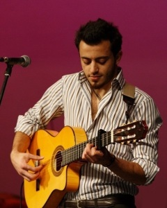 Basel Khoury picture while playing the guitar and performing on stage at a concert 1