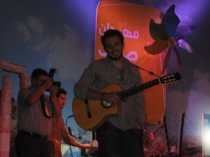 Basel Khoury picture while playing the guitar and performing on stage at a concert 21