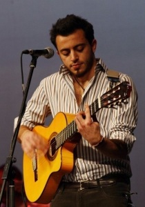 Basel Khoury picture while playing the guitar and performing on stage at a concert 4