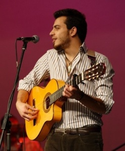 Basel Khoury picture while playing the guitar and performing on stage at a concert 13