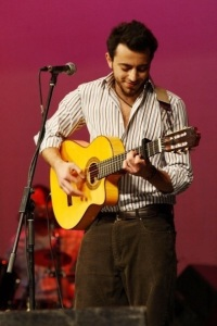 Basel Khoury picture while playing the guitar and performing on stage at a concert 8