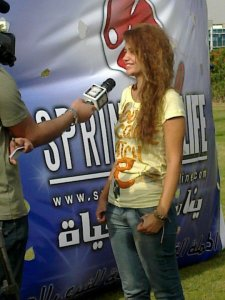 Rania Naguib picture after leaving star academy at an outdoor event while she is also interviewed by tv reporters