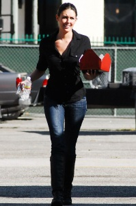 Taylor Cole candid picture while spotted walking the street recently wearing long black boots over denim trousers and a black shirt 5