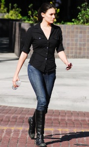 Taylor Cole candid picture while spotted walking the street recently wearing long black boots over denim trousers and a black shirt 1