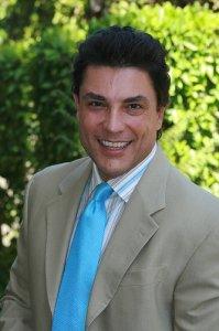 Osvaldo Rios wearing a beige suit