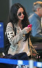 Megan Fox at the airport wearing dark-shaded sunglasses and carrying a pink cell-phone