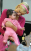 Paris Hilton plays with a customer's baby as she shops for new clothes