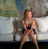 Traci Lords sitting on a white couch