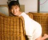 Noriko Sakai photo shoot of her laying on a bamboo couch
