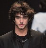 Marlon Teixeira on the runway of a modeling fashion show in a black suit