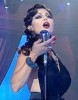 Haifa Wehbe picture during a tv appearance singing on stage in a sixty style makeup and hair wearing a black dress 3
