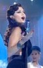 Haifa Wehbe picture during a tv appearance singing on stage in a sixty style makeup and hair wearing a black dress 7