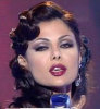 Haifa Wehbe picture during a tv appearance singing on stage in a sixty style makeup and hair wearing a black dress 1