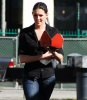 Taylor Cole candid picture while spotted walking the street recently wearing long black boots over denim trousers and a black shirt 3